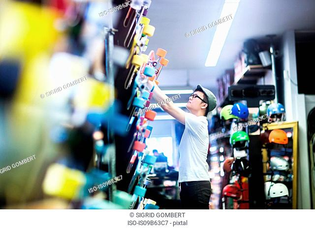 Young male skateboarder removing skateboard from wall in skateboard shop
