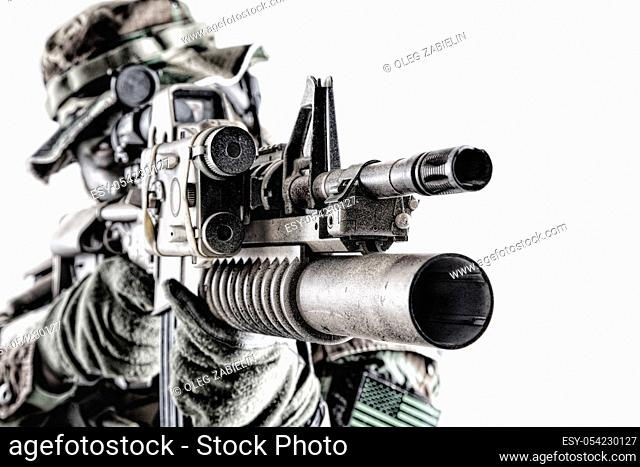 Close up studio shoot of modern commando soldier, US army marine riders shooter looking trough weapon optics, aiming service rifle with laser sight and grenade...