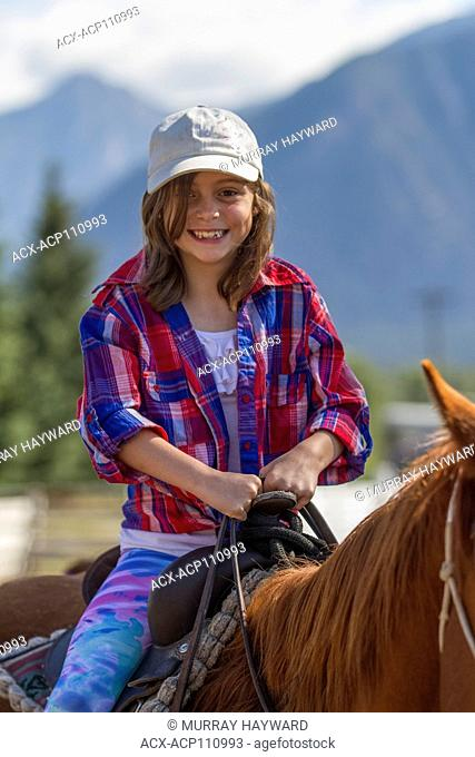 Attractive, young girl, sitting in the saddle, on a trail ride adventure. Looking at camera. Cranbrook, BC, Canada