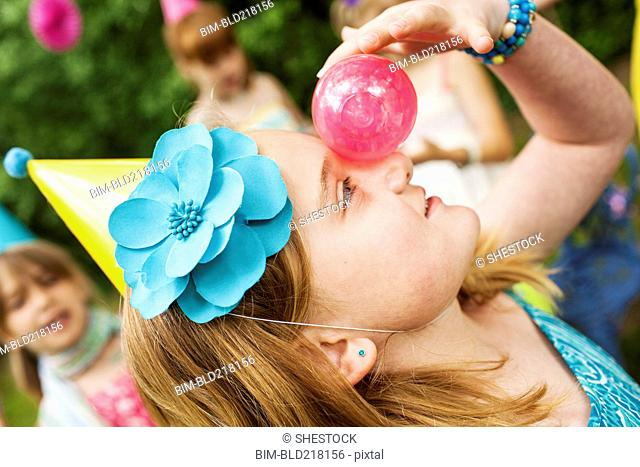 Close up of girl balancing ball on her nose