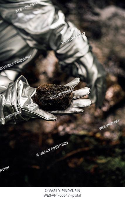 Spaceman exploring nature, holding soil