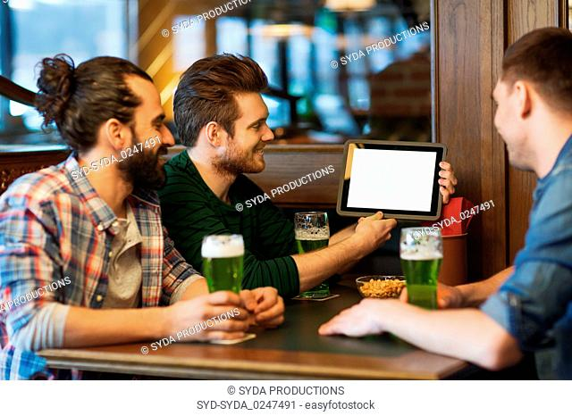friends with tablet pc and green beer at pub