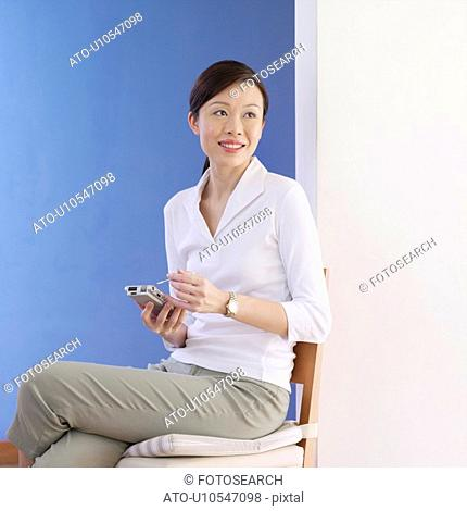 Young woman holding a personal data assistant