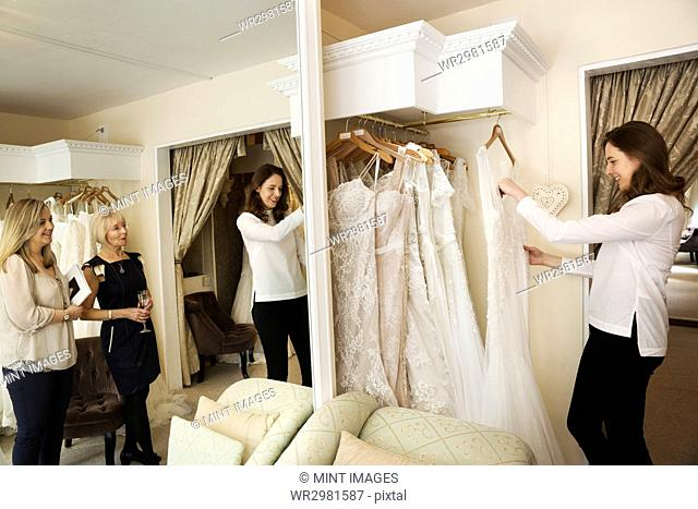 Three women, a client and two retail advisors in a wedding dress shop, looking through the choice of gowns. Large mirror and rows of bridal gowns