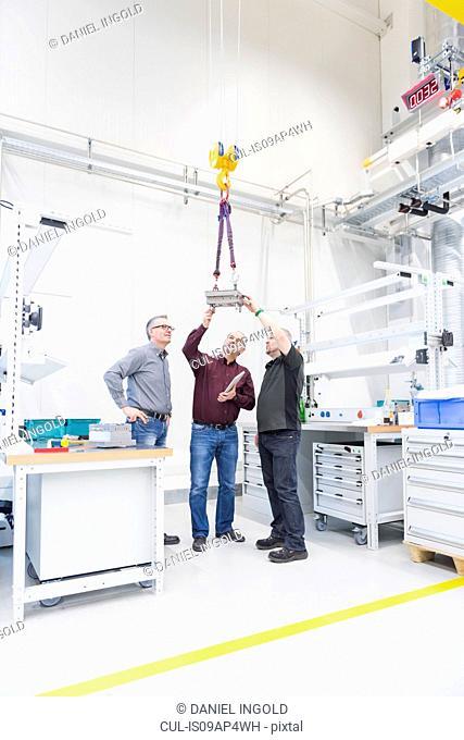 Engineering team looking at hoist in factory