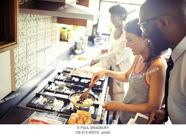 Couple cooking scrambled eggs on stove in kitchen