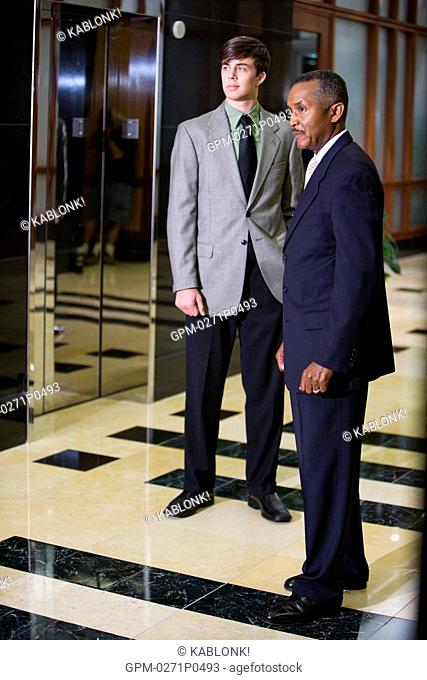 Mature African American businessman with young colleague waiting for elevator in office building lobby