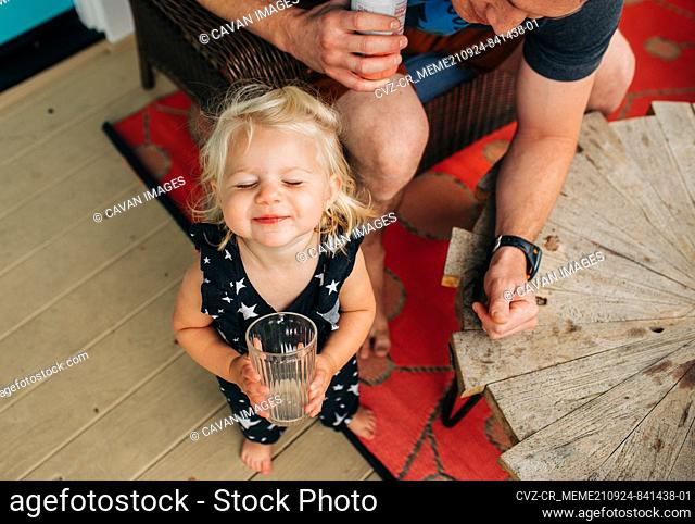 Blonde toddler girl drinks happily from cup while dad watches