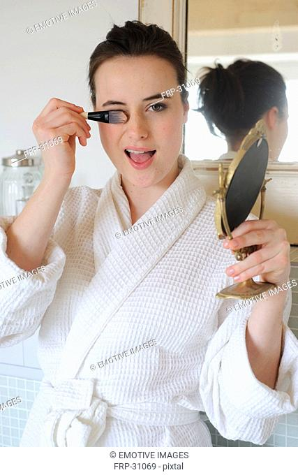 Young woman in bathroom with make-up brush