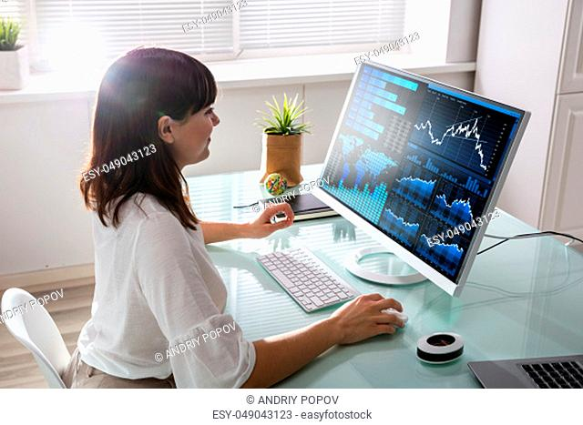 Young Female Stock Market Broker Analyzing Graph On Computer At Workplace