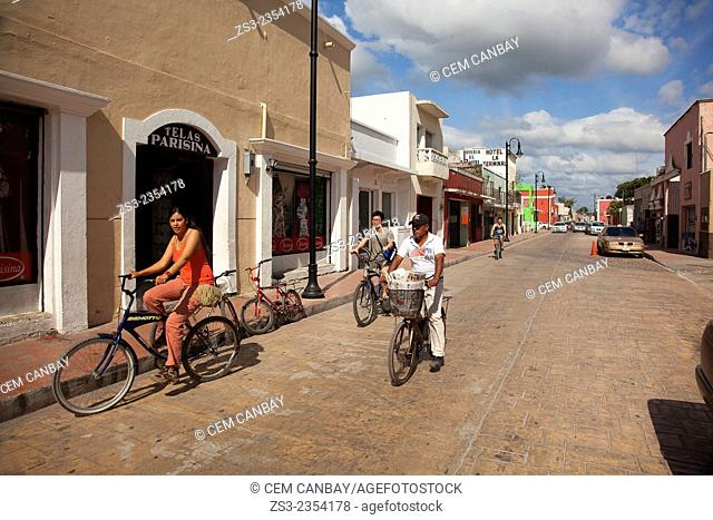 Tourists riding down a street on bikes with traditional buildings in the background, Valladolid, Yucatan Province, Mexico, Central America
