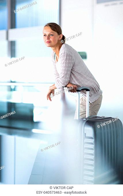 Young female passenger at the airport, about to check-in