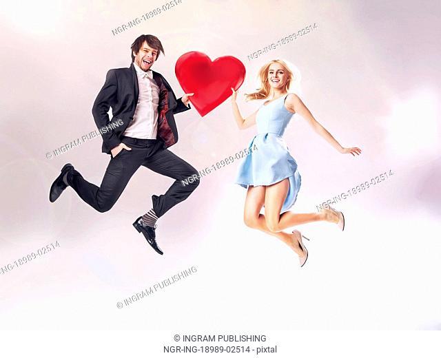Fine photo of cheerful couple holding a cartoon heart