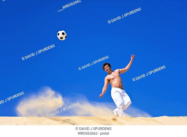 Man playing beach soccer kicks ball