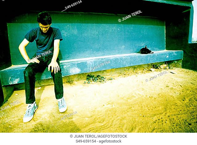 Young man sitting on football bench