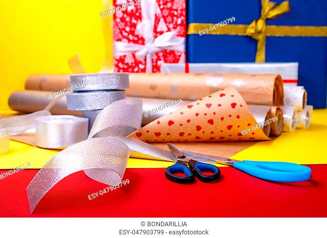 Gift wrapping, boxes, paper, ribbon and scissors on color background. Materials and accessories for wrapping presents. Close up