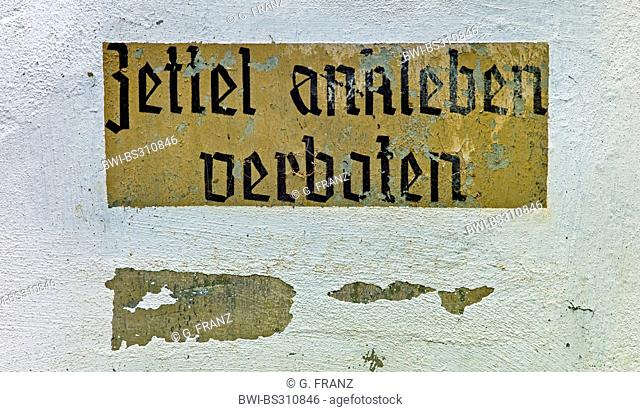 writing 'sticking labels forbidden' at a facade with spalling paint, Germany