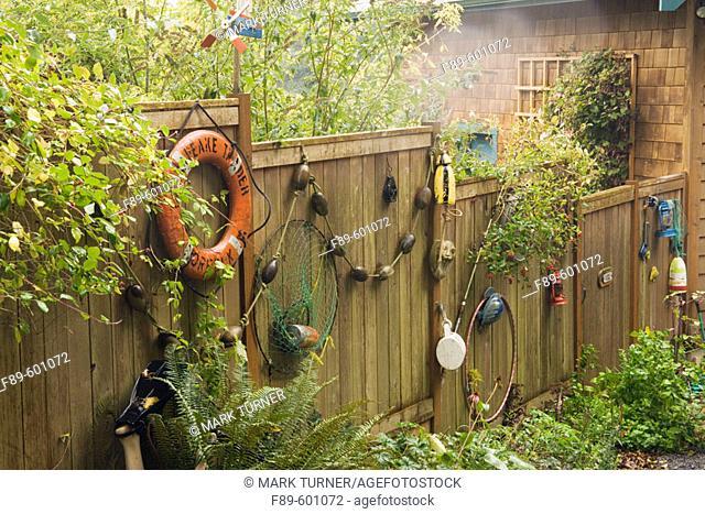 Life preserver, floats, fishing net on wooden fence in rain, autumn (Polystichum munitum). Wall, Lummi Is., WA