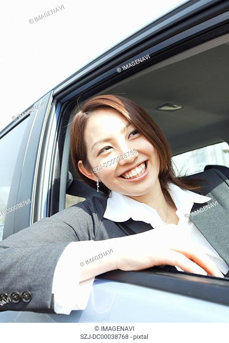 Businesswoman sticking her head out of car window