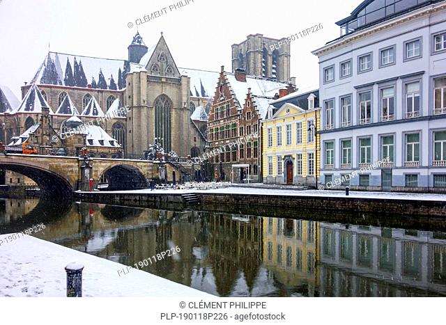 Saint Michael's bridge and the Korenlei along the river Lys / Leie in the snow in winter in the city Ghent, East Flanders, Belgium