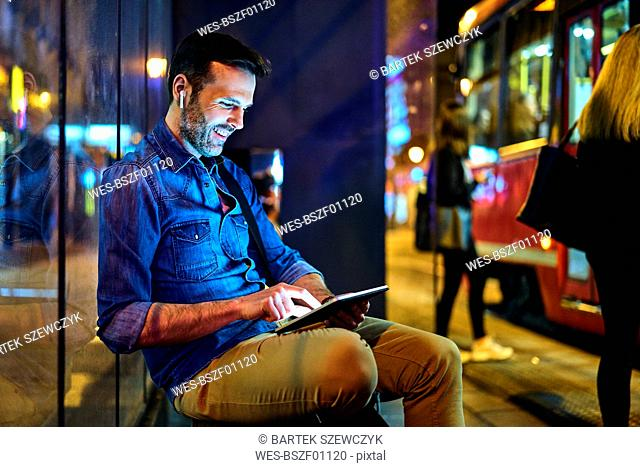 Man with headphones sitting at a station at night using his digital tablet