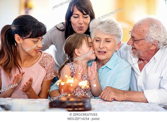 Little girl lwatching sparklers on a birthday cake, sitting on grandmother's lap, with family around