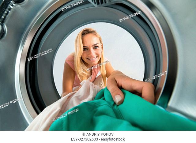 Young Smiling Woman Loading Clothes Inside The Washing Machine