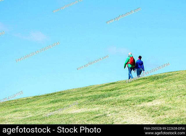 28 May 2020, Lower Saxony, Pilsum: Two tourists walk on the dike in the municipality of Krummhörn. Photo: Hauke-Christian Dittrich/dpa