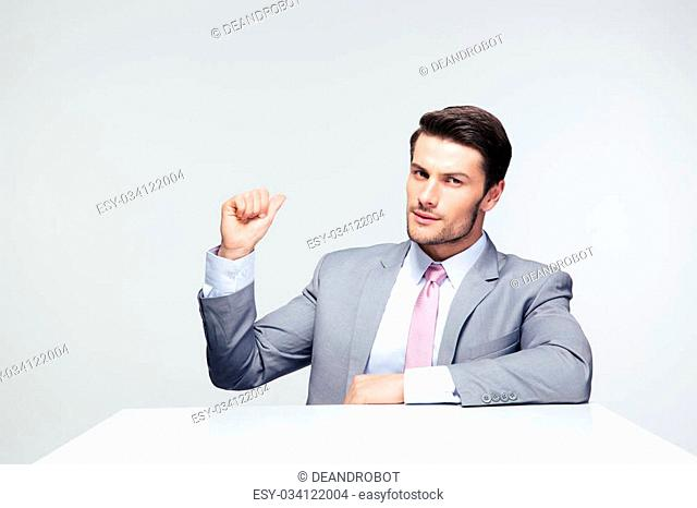 Confident businessman sitting at the table pointing finger back over gray background