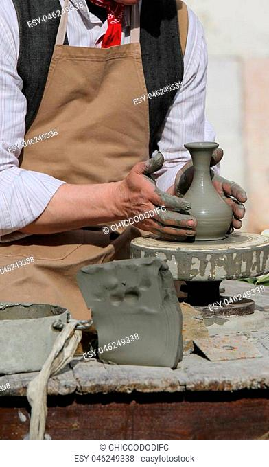 expert potter working with the lathe during manufacture of a delicate clay pot