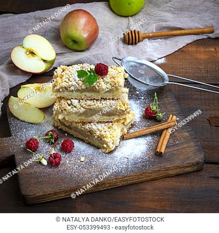 stack of baked slices of pie with apples on a brown wooden board, top view, pastry crumble