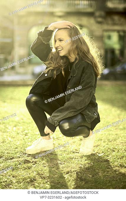young teenager woman outdoors on meadow, happy, in Munich, Germany