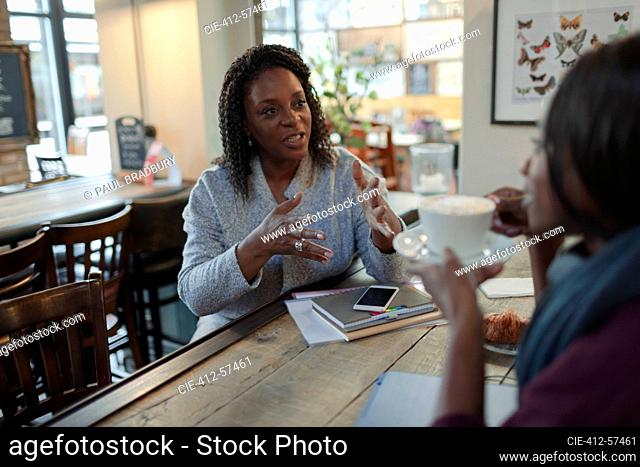 Mother and daughter talking and drinking cappuccino in cafe