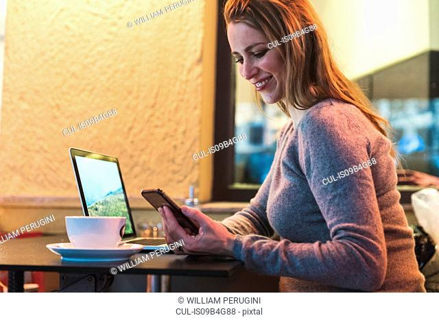 Mid adult woman in cafe looking at smartphone