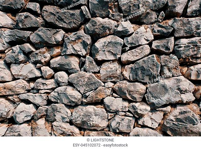 This is a texture of a wall made of single stone blocks. The stones are white to dark gray. They vary in size and shape as they are kept naturally which creates...