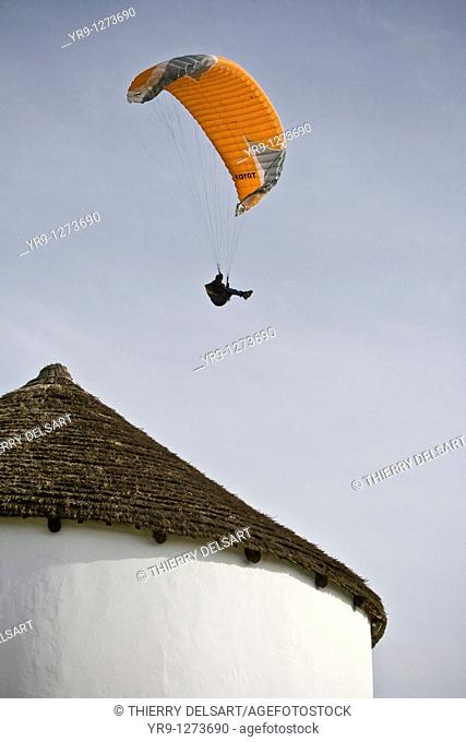 Paraglider approaching the landing spot at Vejer de la Frontera from above the old windmill heather roof