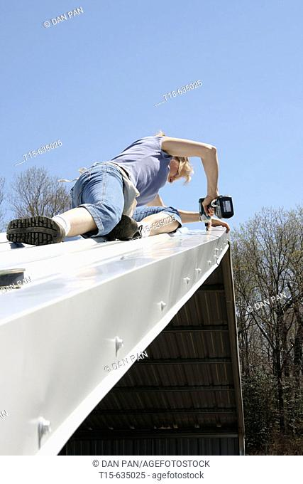 Woman using power drill fixing roof