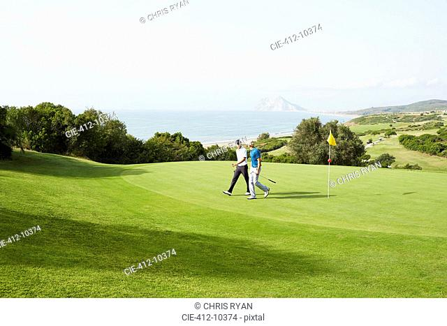 Men walking on golf course overlooking ocean