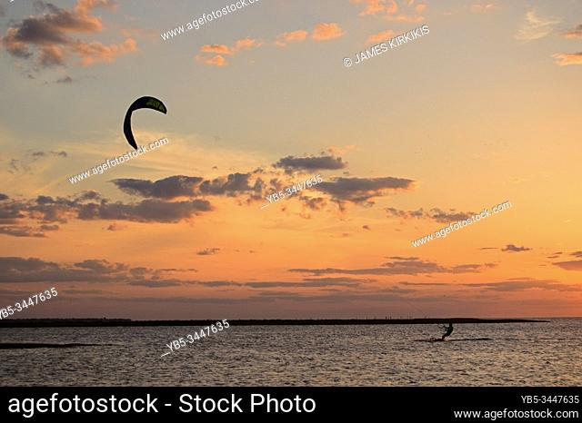 A kite surfer gets in one more ride at sunset