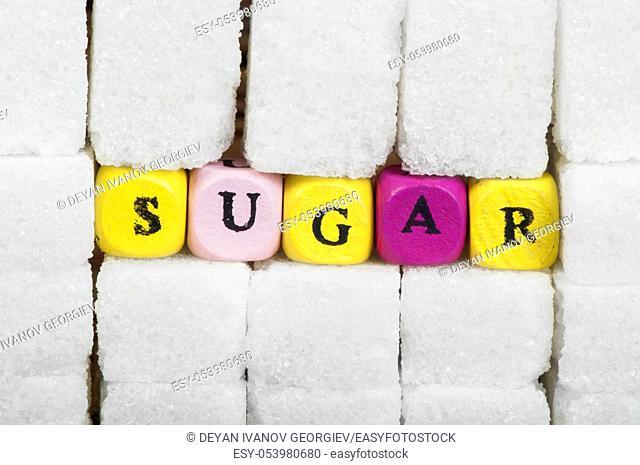 Sugar lumps and word sugar. Multicolored cubes