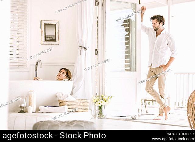 Young man watching woman relaxing in bathtub