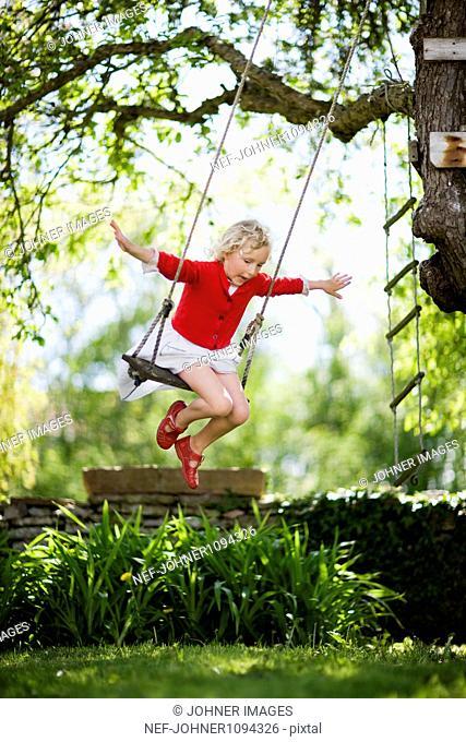 Girl on rope swing in garden
