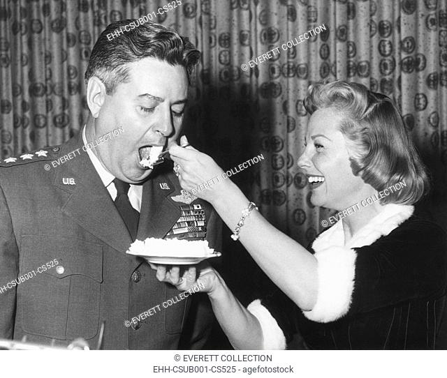 June Allyson serving cake to General Curtis LeMay on the 9th anniversary of SAC. A preview of Allyson's new film, STRATEGIC AIR COMMAND was shown at the party...