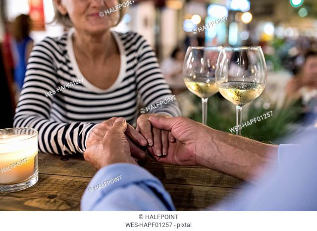 Senior couple hand in hand at an outdoor bar