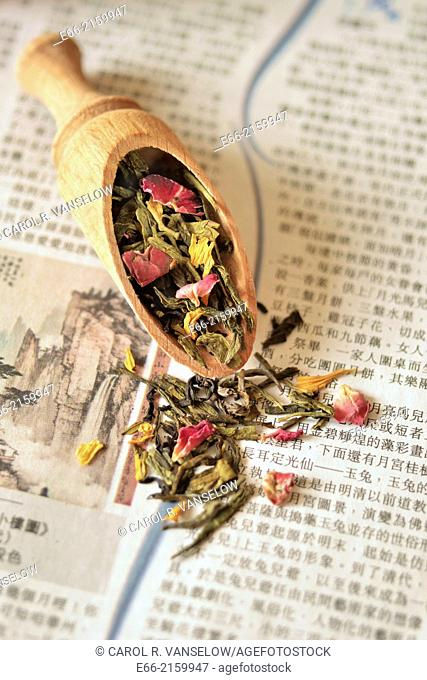 Wooden scoop with green tea blended with dried flowers, laying on Chinese newspaper