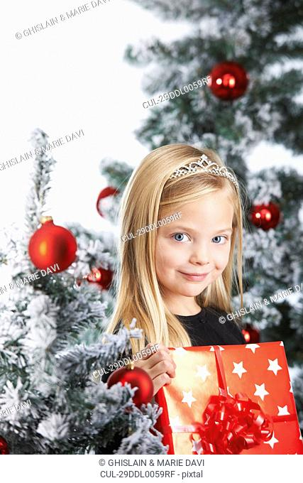Girl by a chritmas tree, with a present