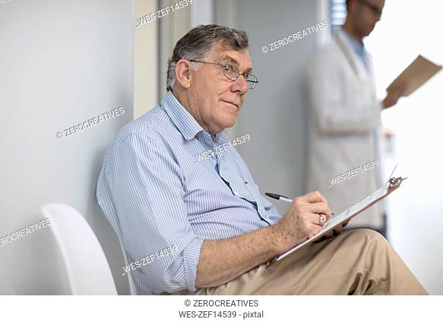 Patient filling in file in medical practice