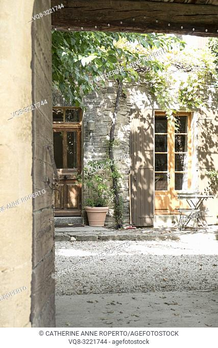 View into sunlit courtyard with vine casting shadows, sweeping brush and cafe table and chair, framed by old, wooden door and light studded lintel in...