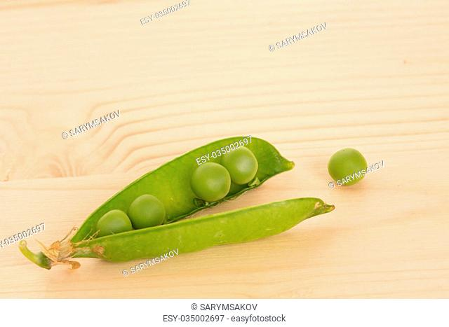 Fresh green peas on a wooden table. Close up