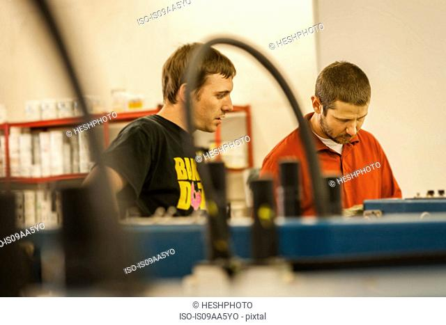 Man watching supervisor in screen print workshop
